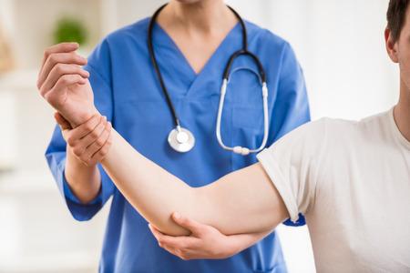 女医が男性患者の腕を伸ばしてのクローズ アップ。