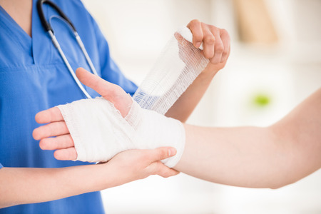 Close-up of female doctor with stethoscope  bandaging hand of male patient. Stockfoto