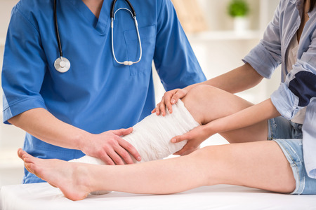 Close-up of male doctor bandaging  foot of female patient at doctors office.