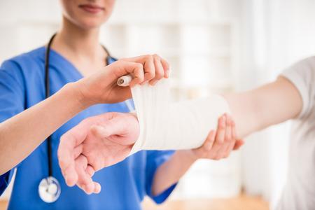 enfermera con paciente: Primer plano de mujer m�dico con estetoscopio vendaje mano del paciente de sexo masculino.