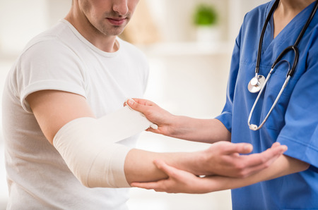 wounded: Close-up of female doctor with stethoscope  bandaging hand of male patient. Stock Photo