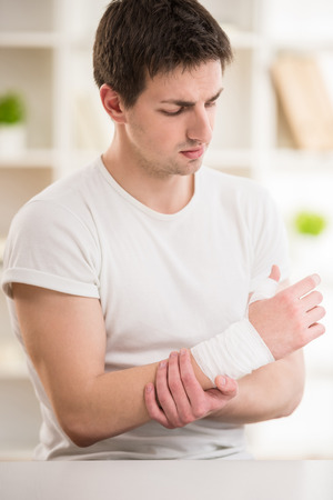 broken arm: Young attractive man with bandage on the hand sitting at doctors office. Stock Photo