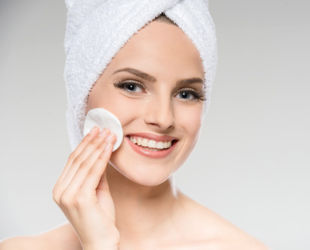 woman in towel: Portrait of beautiful young woman with towel cleaning skin with cotton swab. Stock Photo