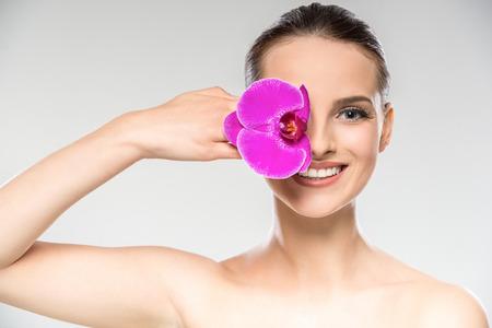 piel humana: Hermoso rostro de mujer joven con la flor púrpura de la orquídea. Tratamiento de cuidado de la piel.