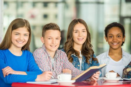Un grupo de adolescentes sentados en la mesa en el café, el estudio y beber té.