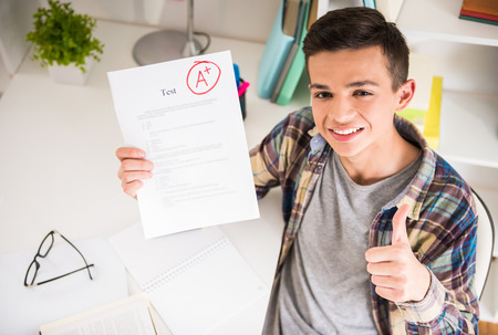 good boy: Portrait of teenager sitting at the table at home and showing perfect test results. Stock Photo