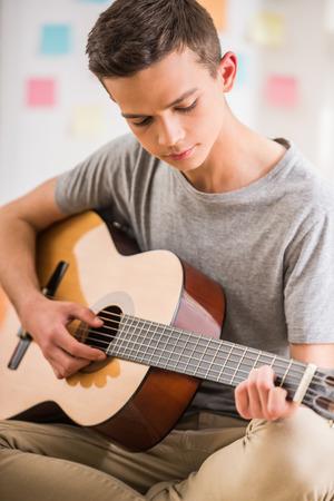 男性のティーンエイ ジャーが自宅で座って、ギターを弾きます。 写真素材