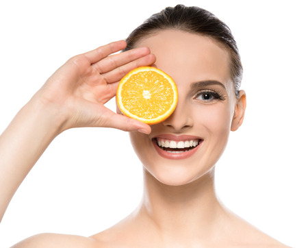 Beautiful young woman with perfect healthy skin and brown hair holding orange. Foto de archivo