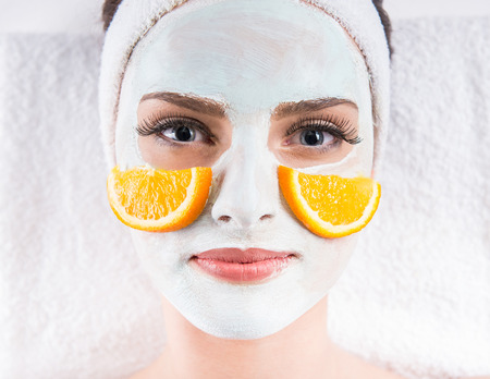 with orange and white body: Young beautiful woman holding orange slices and mask on the face in a spa salon. Stock Photo