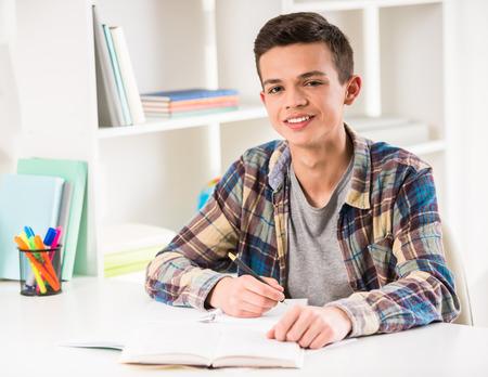 젊은 웃는 소년 테이블에 앉아 집에서 숙제.