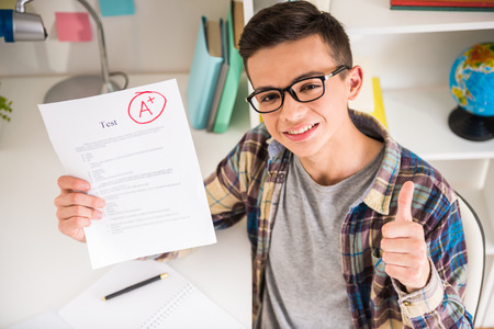best result: Portrait of teenager sitting at the table at home and showing perfect test results. Stock Photo