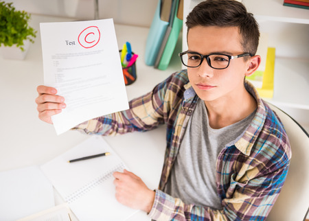 angry teacher: Male teenager sitting at the table at home and showing bad test results. Stock Photo