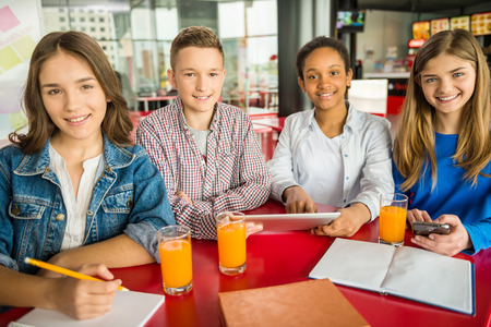 A group of teenagers sitting at the table in cafe, studying and drinking orange juice.