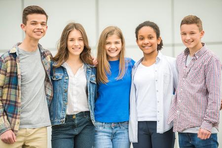 Groep van lachende vrolijke tieners plezier na de lessen.