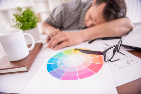 tired: Tired working man sleeping at the workplace full of sketches. Stock Photo