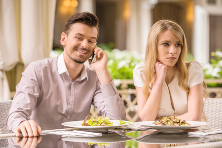Woman is getting bored in restaurant while her boyfriend is talking on the phone. Stock Photo