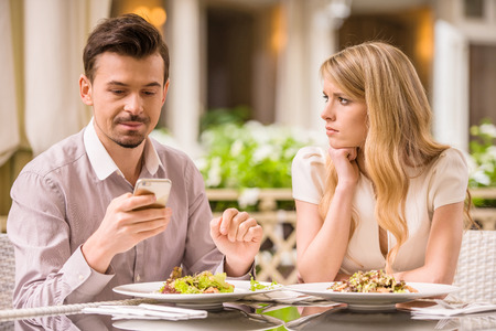relationship problems: Young smiling couple in gorgeous restaurant. Man looking at phone.