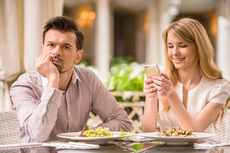 annoyed: Man is getting bored in restaurant while his woman looking at phone. Stock Photo