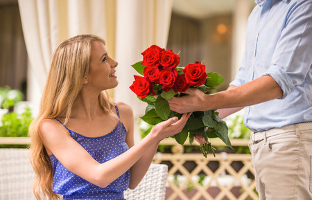 woman: Man surprising his cute girlfriend with flowers on romantic date.