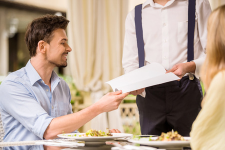Cheerful couple with menu in a restaurant making order. Romantic dinner. photo