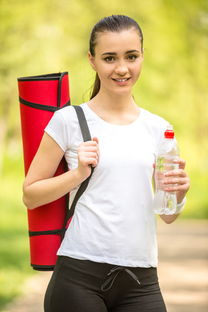 Attractive sporty girl holding mat for yoga. Morning outdoor training. photo