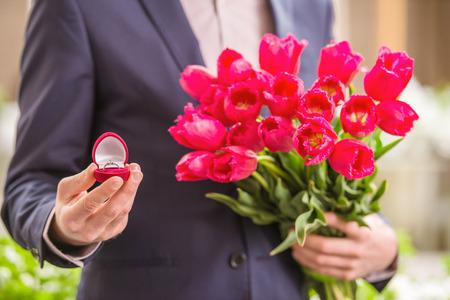 casamento: Close-up do homem que prende o ramalhete de tulipas e caixa de presente com anel. Proposta.