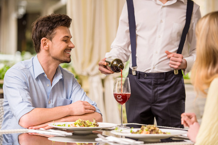 Cheerful couple in a restaurant ordering wine. Romantic dinner.