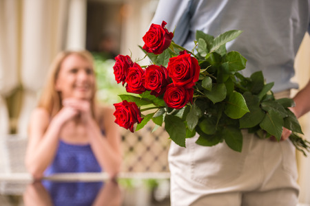birthday adult: Young woman looking at man with flower bouquet behind the back. Stock Photo