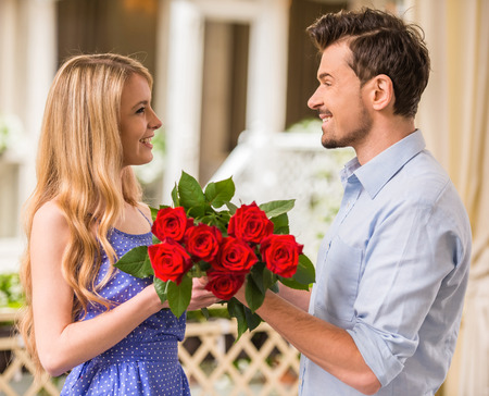 girl holding flower: Happy young couple with roses bouquet on a date.