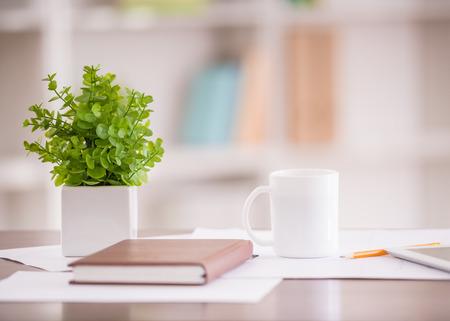 taza: Primer plano de la mesa en la oficina de negocios con el diario, el l�piz y la taza de caf�.