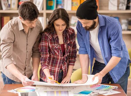reunion de trabajo: Tres diseñadores creativos jóvenes que trabajan en proyecto juntos. El trabajo en equipo.