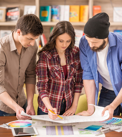 Three young creative designers discussing draft. Team work. photo