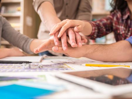 personas trabajando en oficina: Grupo creativo de diseñadores que ponen las manos juntas. El trabajo en equipo.