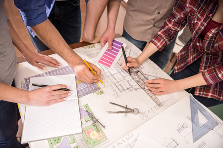 Close-up of creative architects working at draft in office. photo