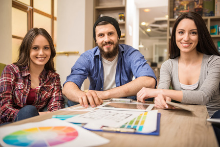 jovenes felices: Grupo creativo de dise�adores que discuten proyecto en la oficina. Foto de archivo