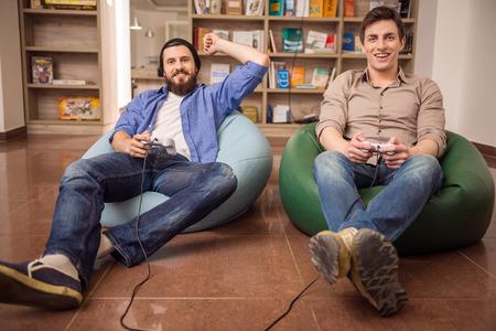 Dos chicos guapos jóvenes sentados en pufs y jugando juegos de video juntos. Tiempo libre.