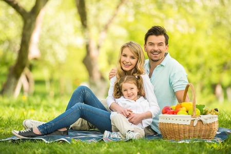Afbeelding van gelukkige jonge gezin met picknick buitenshuis. Stockfoto