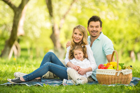 man outdoors: Image of happy young family having picnic outdoors. Stock Photo