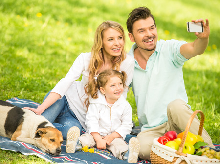 Image of happy young family having picnic outdoors and making selfie.