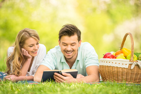 summer fun: Young beautiful couple dressed casual lying on the lawn in summer park. Man reading for woman. Stock Photo