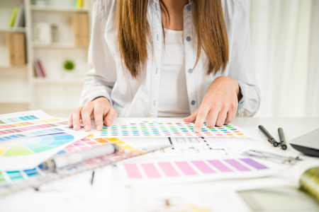 Close-up of young designer working with color samples in her office. Stok Fotoğraf - 40612286