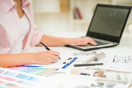 trabajando en casa: Primer plano de la joven y bella dise�ador usa la computadora port�til en su oficina.