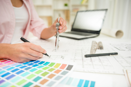 Close-up de la designer d'intérieur travaillant avec plan architectural avec boussole. Banque d'images - 40251535