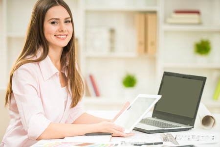 home office interior: Young interior designer holding digital tablet in hands and working in her modern home office. Stock Photo