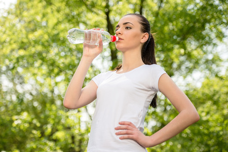 Beautiful sporty girl in white t-shirt drinking water. Training in park. photo