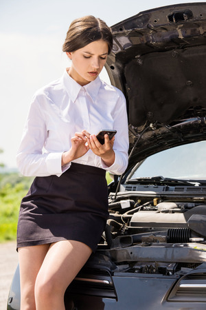 waiting phone call: Businesswoman standing near broken car and calling for help on phone. Stock Photo