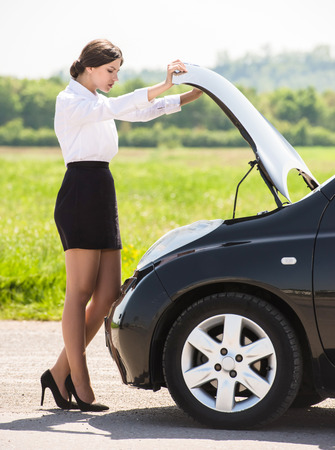Side view of young businesswoman examining broken down car engine at countryside.