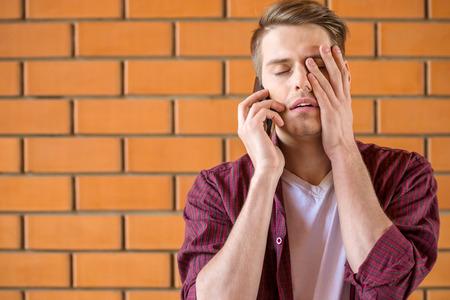 personas dialogando: Hombre cansado joven hablando por teléfono sobre fondo de pared de ladrillo. Foto de archivo