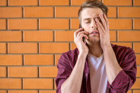upset: Young tired man talking on phone on brick wall background.