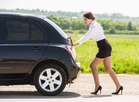 Young businesswoman pushing a car with empty fuel tank.